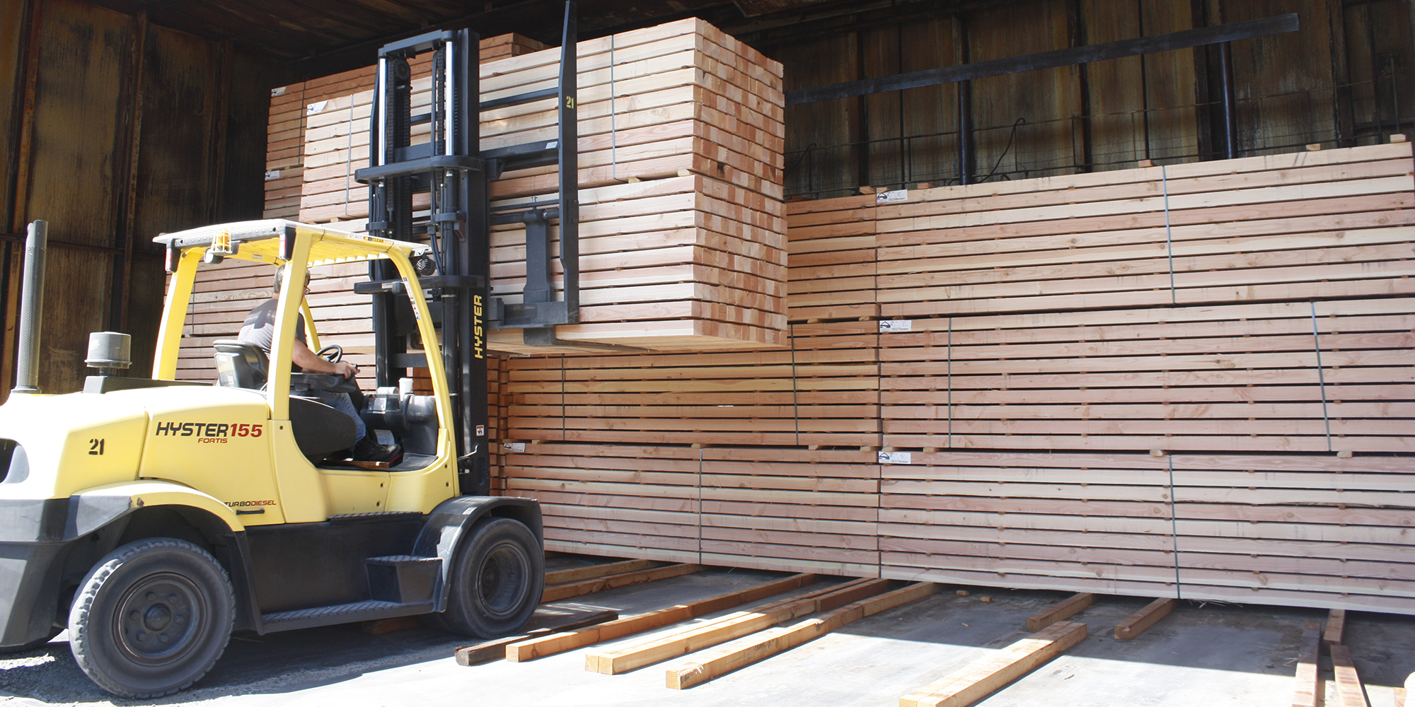 Forklift lifting wood in Clackamas Business