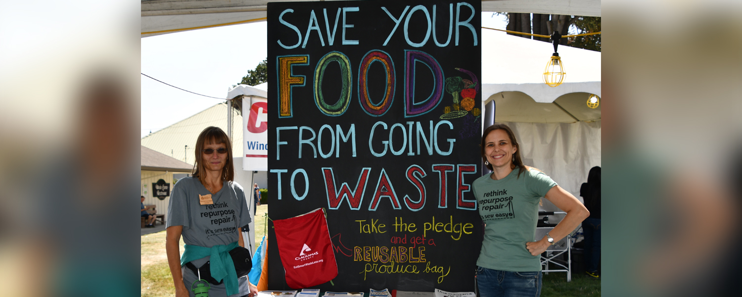 "Two women standing in front of a sign that says ""Save your food from going to waste"""