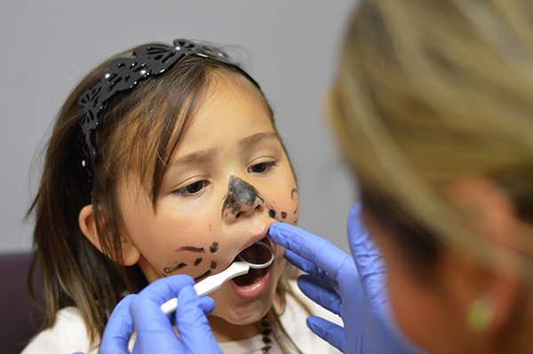 Little girl with her face painted like a kitty cat gets her teeth checked by a dentist.