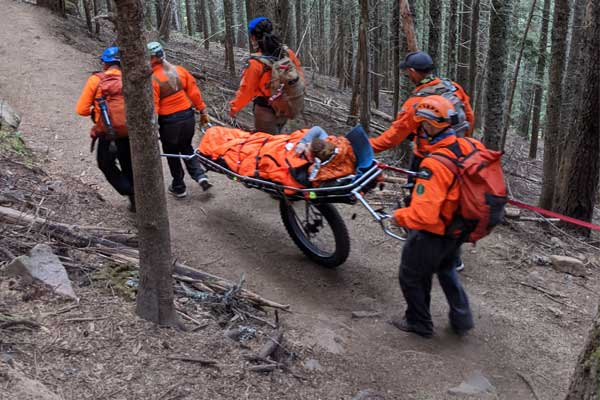 Search and Rescue volunteers move an injured person on a mountain trail