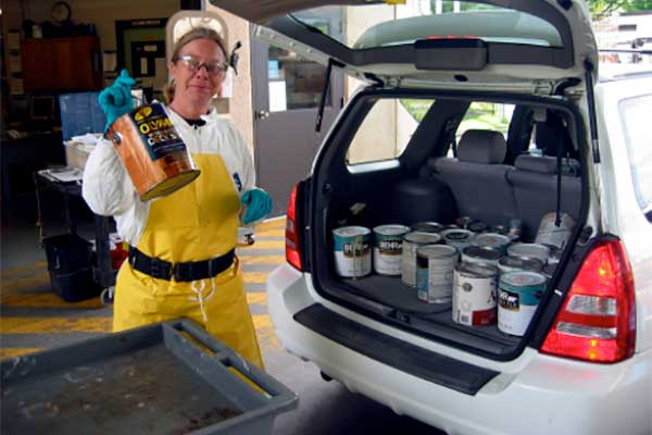 woman removes hazardous waste from car
