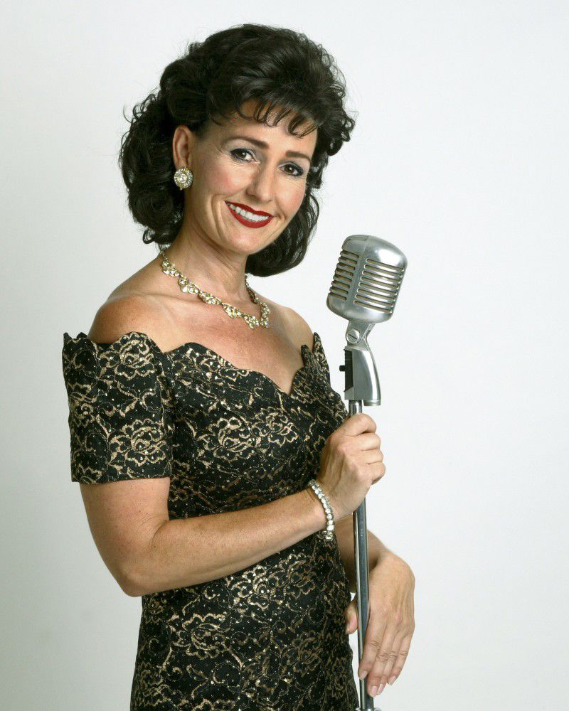 Jeanne Coady holding an old fashioned microphone