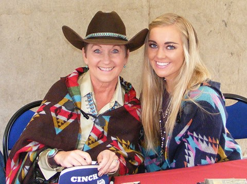Joni Harms and Olivia Harms Wichman sitting at a table. Joni is where a cowgirl hat.