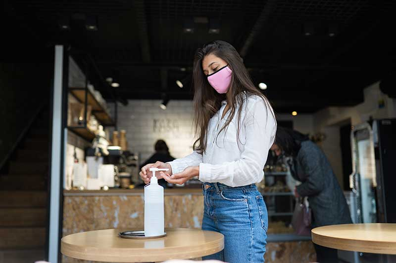 Woman wearing mask and using hand sanitizer at a business