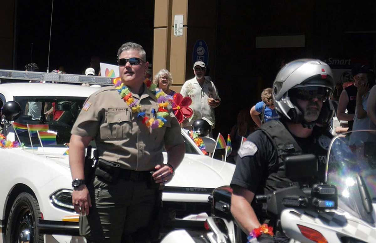 Sheriff's Deputy with flowered lei at the Pride Parade