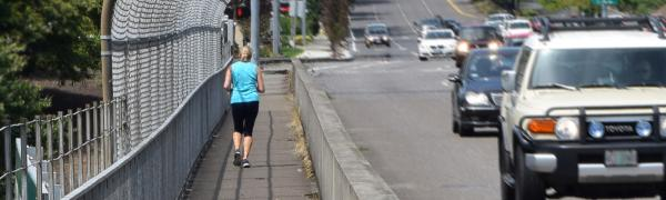 A woman jogging safely on a sidewalk beside a busy street.