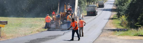 Workers paving a road on a summer day.