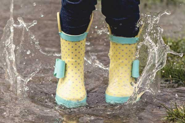 Playing in the rain while wearing yellow rainboots